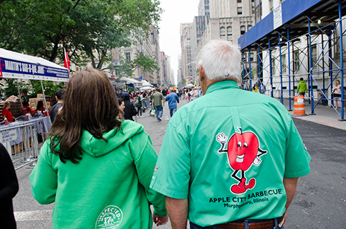 "Amy Mills and Mike Mills walking to the ""rib-bon"" cutting ceremony kicking off the Big Apple Barbecue Block Party."